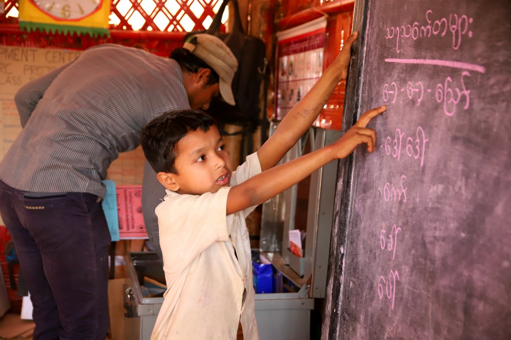 Shukhon wants to be a teacher when he grows up and often volunteers to lead his class in reading and writing. Photo: WFP/Gemma Snowdon.