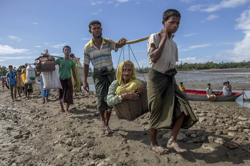 Rohingya Muslims, who crossed over from Myanmar into Bangladesh, carry an elderly woman in a basket and walk towards a refugee camp in Shah Porir Dwip, Bangladesh, Thursday, Sept. 14, 2017.