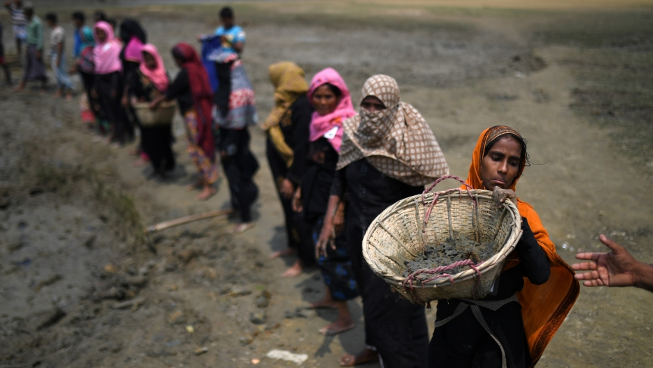 Rohingya refugee women carry baskets of dried out mud from the riverbed to help raise the ground level of the camp in preparation for monsoon season, in Shamlapur refugee camp in Cox's Bazaar, Bangladesh, March 24, 2018.  Credit: Clodagh Kilcoyne/Reuters