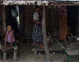 A Rohingya Muslim family stand in front of their house at Pan Taw Pyin village in Maungdaw in Myanmar's northern Rakhine state. AFP