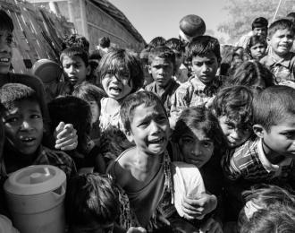 Rohingya refugee children cry and struggle in the crowd as they wait to receive food outside a distribution point of the Turkish aid organization TIKA at the Jamtoli refugee camp near Cox's Bazar, Bangladesh, December 01, 2017. (Photo by Szymon Barylski/NurPhoto via Getty Images)