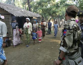 In this photo, Muslim refugees walk as Burma police officers stand guard at Sin Thet Maw relief camp in Pauktaw township, Rakhine state, western Burma. (AP)