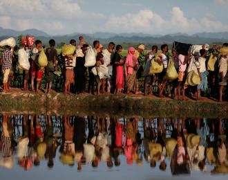 Rohingya refugees who fled from Myanmar wait to be let through by Bangladeshi border guards after crossing the border in Palang Khali, Bangladesh October 9, 2017. REUTERS/Damir Sagolj