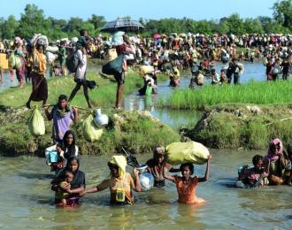 Rohingya refugees walk through a shallow canal after crossing the Naf River to reach Bangladesh